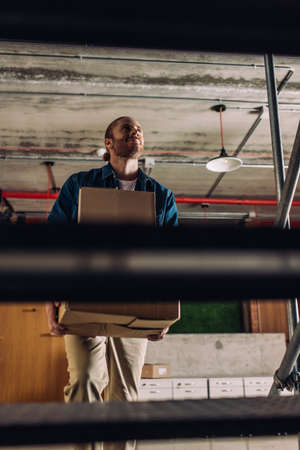 selective focus of happy businessman holding boxes while walking on stairs in office