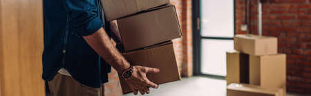 panoramic crop of businessman holding boxes and moving in new office