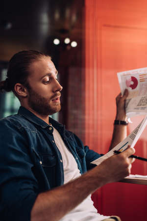 selective focus of handsome and bearded businessman looking at charts and graphs
