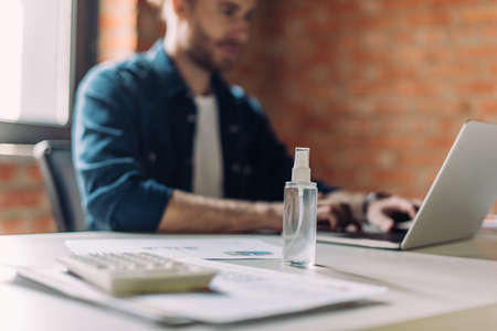 selective focus of bottle with hand sanitizer near businesswoman using laptop in office