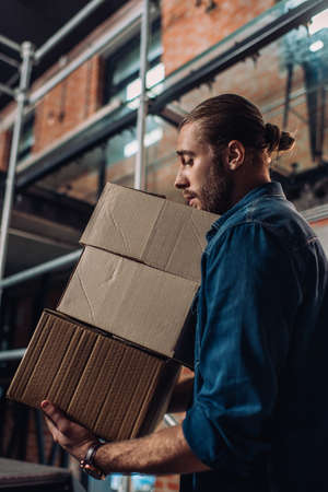 selective focus of bearded businessman looking at carton boxes in new office