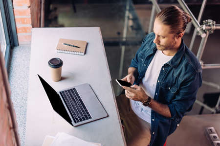 high angle view of businessman using smartphone near laptop and disposable cup