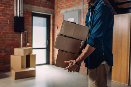 cropped view of businessman holding boxes and moving in new office