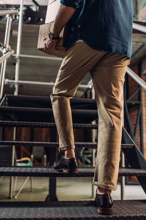 cropped view of businessman holding boxes while walking on stairs in office