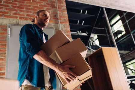 low angle view of man holding boxes while moving in new office