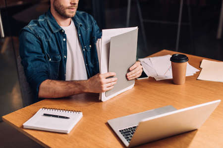 cropped view of businessman holding folder near gadgets and paper cup on desk