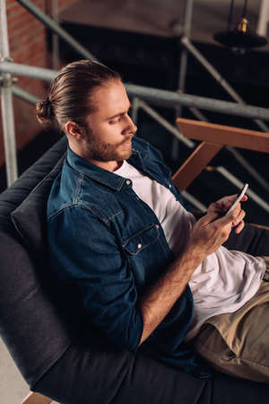 handsome businessman chilling on sofa and using smartphone in office Reklamní fotografie