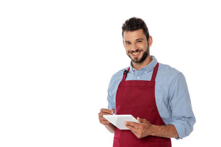 Smiling waiter looking at camera while using digital tablet isolated on white