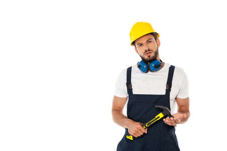 Handsome workman in uniform and hardhat holding hammer and looking at camera isolated on white