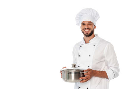 Handsome chef smiling at camera while holding pan isolated on white