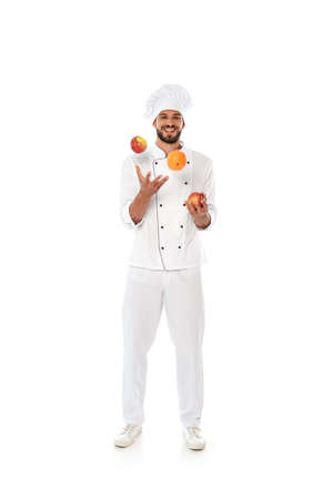 Smiling chef juggling fresh fruits on white background