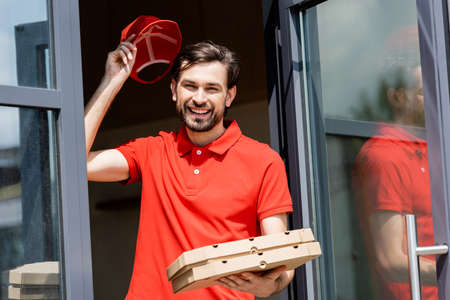 Positive waiter holding pizza boxes and cap near cafe