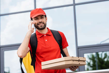 Smiling delivery man looking at camera while holding pizza boxes and talking on smartphone on urban street Banco de Imagens