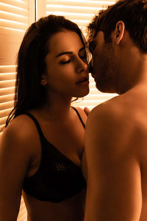 handsome man touching sensual woman with closed eyes