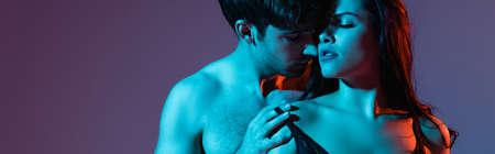 horizontal image of shirtless man touching bra of sexy woman on purple