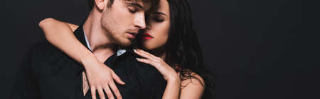 panoramic shot of sexy young woman hugging passionate boyfriend isolated on black