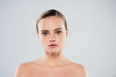 young woman looking at camera isolated on gray