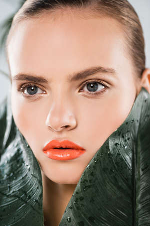 close up of beautiful girl with makeup near green and wet leaves