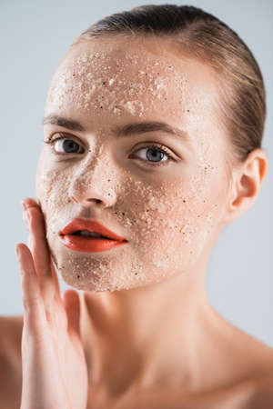 close up of young woman applying scrub isolated on white Imagens