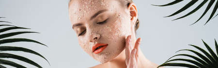 panoramic shot of woman applying scrub near palm leaves on white 版權商用圖片
