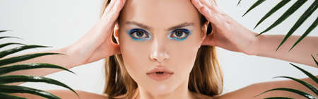 horizontal crop of beautiful woman with blue eye shadow looking at camera near palm leaves on white