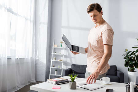 Man holding laptop and looking at notebook on table at home, earning online concept