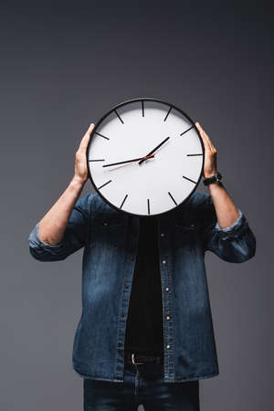Young man holding clock near face on gray background, concept of time management