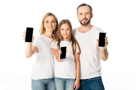 smiling family in white t-shirts showing smartphones with blank screens isolated on white
