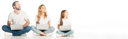 family sitting on floor with laptops on crossed legs and looking away isolated on white, panoramic shot