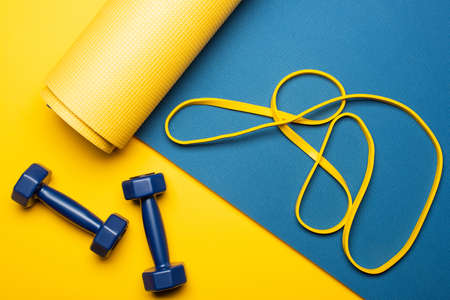 top view of blue fitness mat with dumbbells and resistance band on yellow background 免版税图像