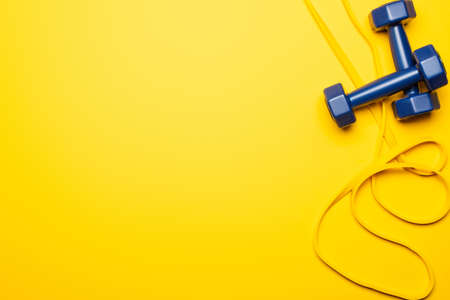 top view of blue dumbbells and resistance band on yellow background