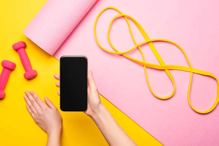 cropped view of woman holding smartphone near resistance band on pink fitness mat and dumbbells on yellow background