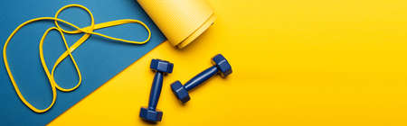 top view of blue fitness mat with dumbbells and resistance band on yellow background, panoramic shot