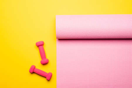 top view of pink fitness mat and dumbbells on yellow background 免版税图像