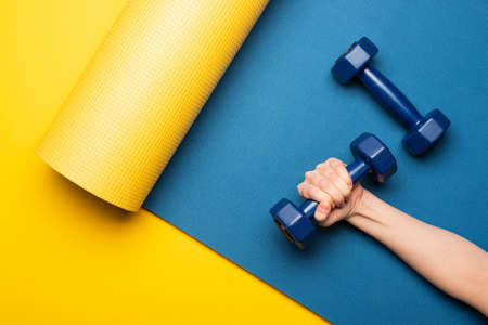 cropped view of woman holding dumbbell on blue fitness mat on yellow background