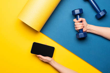 cropped view of woman holding dumbbell and smartphone on blue fitness mat on yellow background