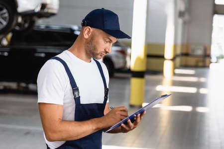 handsome mechanic in uniform holding clipboard