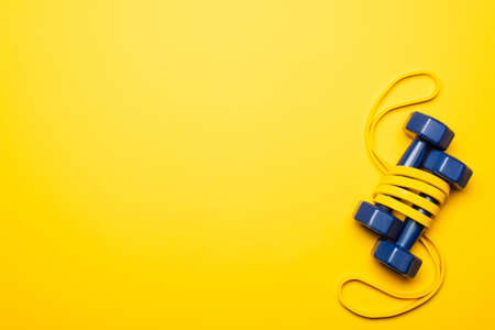 top view of blue dumbbells in resistance band on yellow background 免版税图像