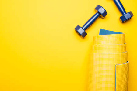 top view of rolled fitness mat and blue dumbbells on yellow background 免版税图像