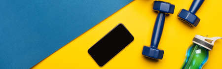 top view of blue fitness mat with dumbbells, smartphone and sports bottle on yellow background, panoramic shot 免版税图像