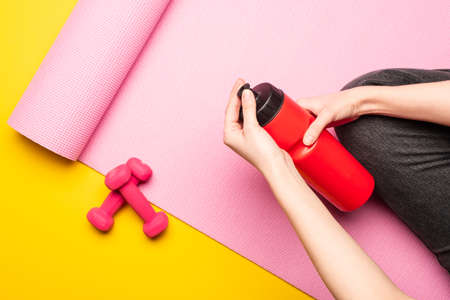 partial view of woman holding sports bottle while sitting on pink fitness mat near dumbbells on yellow background