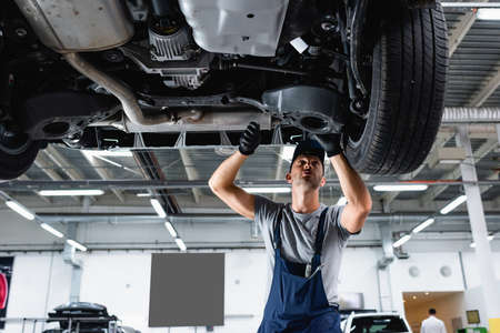 low angle view of technician in cap and overalls repairing car in service station Reklamní fotografie