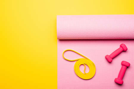 top view of pink dumbbells and elastic band on pink fitness mat on yellow background