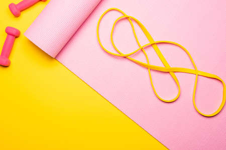 top view of resistance band on pink fitness mat near dumbbells on yellow background
