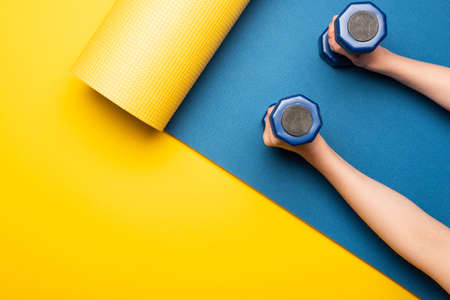 cropped view of woman holding dumbbells on blue fitness mat on yellow background