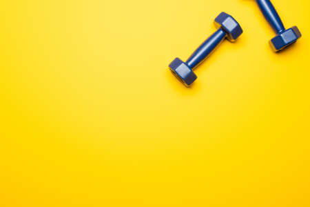 top view of blue dumbbells on yellow background 免版税图像