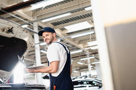 Happy auto mechanic holding laptop at service station