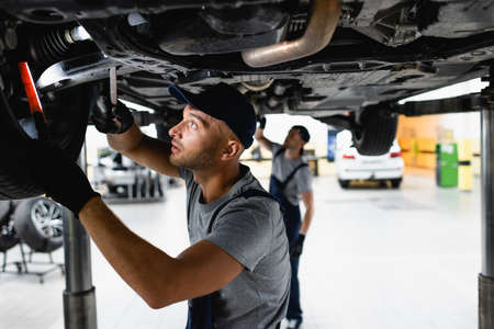 selective focus of handsome mechanic in cap holding flashlight and wrench while fixing car near coworker in service station