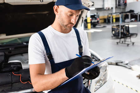 Auto mechanic writing on clipboard near open hood of car at service station