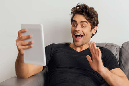 Selective focus of cheerful man waving hand while having video call on digital tablet on couch on gray background